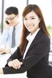 Ung affärskvinna med kollegan i regeringsställning arkivfoto