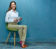 Ung affärskvinna med minnestavlasammanträde på stol arkivfoton