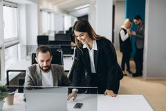 Ung affärskvinna och affärsman som arbetar samman med kontorsarbetare på bakgrund i modernt kontor fotografering för bildbyråer