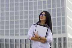 Ung affärskvinna på bakgrund av skyskrapan Arkivbild