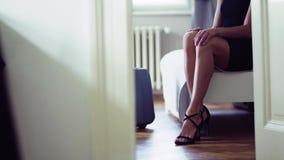 Ung affärskvinna på en affärstur som sitter i ett hotellrum som sätter på skor stock video