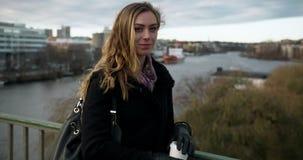 Ung affärskvinna på en bro i centrala Stockholm, vänd och blickar på kameran arkivfilmer