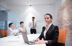 Ung affärskvinna på möte genom att använda bärbar datordatoren Arkivbild