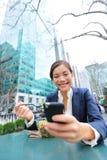 Ung affärskvinna på smartphonen i lunchavbrott Arkivbild