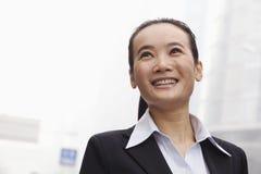 Ung affärskvinna Smiling och se in i avståndet Royaltyfri Foto