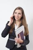 Ung affärskvinna som är upptagen med en bärbar dator och legitimationshandlingar som talar på telefonen Royaltyfri Bild