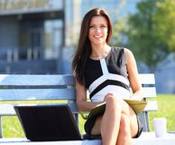 Ung affärskvinna som använder bärbara datorn Royaltyfri Fotografi