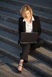 Ung affärskvinna som använder bärbara datorn på momenten Royaltyfri Bild
