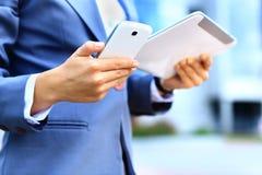 Ung affärskvinna som använder den digitala minnestavlan och mobiltelefonen Arkivfoton