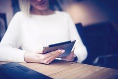 Ung affärskvinna som använder den digitala minnestavlan på trätabellen Begrepp av coworking folkarbete med mobila enheter Royaltyfri Fotografi
