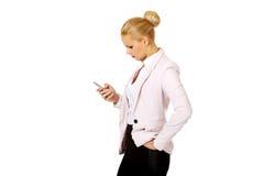 Ung affärskvinna som använder en mobiltelefon Fotografering för Bildbyråer