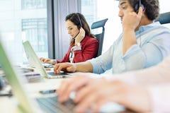 Ung affärskvinna som använder hörlurar med mikrofon och bärbara datorn med kollegor i förgrund på kontoret arkivfoto