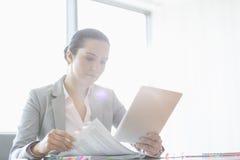 Ung affärskvinna som använder minnestavlaPC medan läsebok i regeringsställning Arkivbild