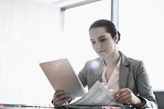Ung affärskvinna som använder minnestavlaPC medan läsebok i regeringsställning Arkivfoto