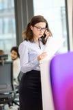 Ung affärskvinna som använder mobiltelefonen medan läsebok i regeringsställning Arkivfoto