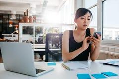 Ung affärskvinna som använder mobiltelefonen på arbete Royaltyfri Fotografi