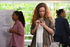 Ung affärskvinna som använder smartphonen i kontoret med kollegor i bakgrunden royaltyfria bilder