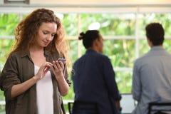 Ung affärskvinna som använder smartphonen i kontoret med kollegor i bakgrunden royaltyfri foto