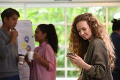 Ung affärskvinna som använder smartphonen i kontoret med kollegor i bakgrunden arkivbild