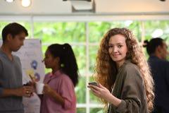 Ung affärskvinna som använder smartphonen i kontoret med kollegor i bakgrunden arkivbilder
