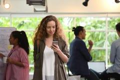 Ung affärskvinna som använder smartphonen i kontoret med kollegor i bakgrunden royaltyfri fotografi
