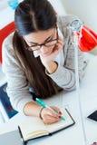 Ung affärskvinna som arbetar i hennes kontor med bärbara datorn Arkivbild