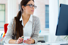 Ung affärskvinna som arbetar i hennes kontor med bärbara datorn Royaltyfri Bild