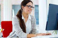 Ung affärskvinna som arbetar i hennes kontor med bärbara datorn Arkivbilder