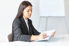 Ung affärskvinna som arbetar i kontoret Arkivfoton