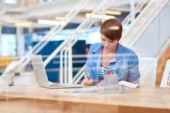 Ung affärskvinna som arbetar på det moderna skrivbordet bak exponeringsglas Royaltyfri Fotografi