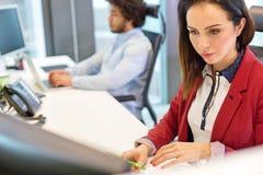 Ung affärskvinna som arbetar på skrivbordet med den manliga kollegan i bakgrund arkivfoto