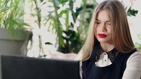 Ung affärskvinna som bläddrar materielnyheterna på internet på en bärbar dator stock video