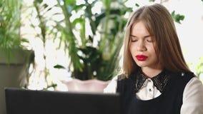 Ung affärskvinna som bläddrar materielnyheterna på internet på en bärbar dator lager videofilmer