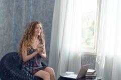 Ung affärskvinna som dricker kaffe med bärbara datorn på tabellen Royaltyfria Foton