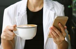 Ung affärskvinna som dricker kaffe och använder den smarta telefonen i kafét, affärskvinna som arbetar på hennes kaffeavbrott i k arkivfoton
