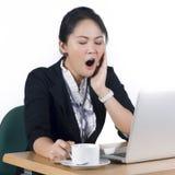 Ung affärskvinna som gäspar på henne skrivbordet Royaltyfria Bilder