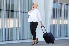 Ung affärskvinna som går med resväskan Royaltyfri Bild