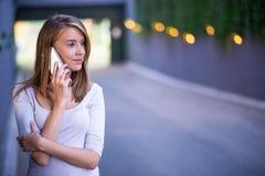 Ung affärskvinna som gör en påringning på hennes smarta telefon Arkivbild