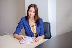 Ung affärskvinna som i regeringsställning arbetar på skrivbordet och att ta anmärkningar in i den personliga kalendern som ler royaltyfri bild