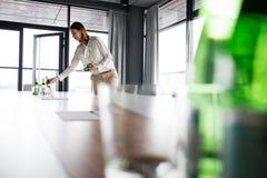Ung affärskvinna som i regeringsställning förlägger vattenflaskor på konferenstabellen Arkivbilder