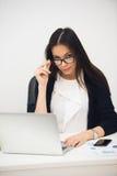 Ung affärskvinna som i regeringsställning sitter att arbeta Le och se kameran royaltyfri fotografi