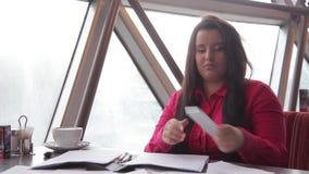 Ung affärskvinna som i regeringsställning talar på mobiltelefonen lager videofilmer