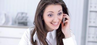 Ung affärskvinna som i regeringsställning talar på mobiltelefonen royaltyfri bild