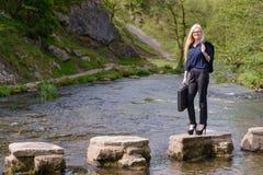 Ung affärskvinna som kliver stenar till framgångmetaforen Royaltyfria Foton