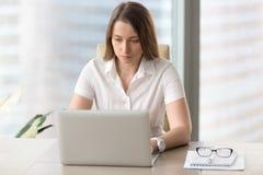 Ung affärskvinna som koncentreras på dagliga uppgifter arkivfoto