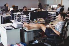 Ung affärskvinna som kopplar av medan kollegor som i regeringsställning arbetar arkivbilder