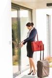 Ung affärskvinna som låser lämna för bagage för dörr resande Royaltyfria Foton