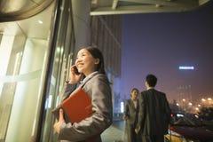 Ung affärskvinna som ler, går och talar på hennes mobiltelefon på natten Arkivfoton