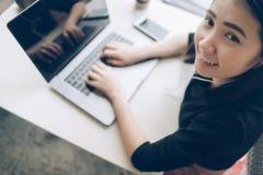 Ung affärskvinna som ler genom att använda bärbara datorn på trätabellen, medan sitta i coffee shop, bästa sikt arkivfoton