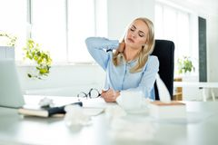 Ung affärskvinna som lider influensa på arbete arkivfoton
